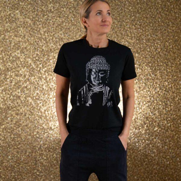 Frau vor goldener Wand mit schwarzem Tshirt mit Buddha Aufdruck. Von Natural Born Yogi.