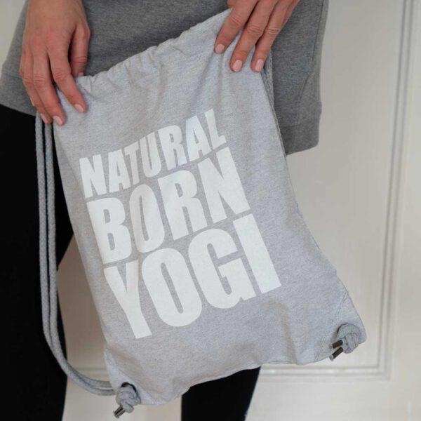 Grauer Yoga Gymbag aus Stoff mit Natural Born Yogi Aufdruck.