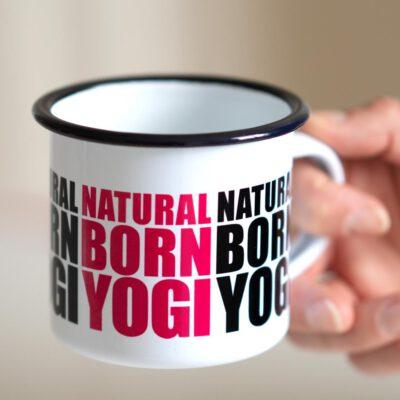 Weisse Emailletasse mit Natural Born Yogi Aufdruck.